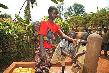 Burundi woman and her sons collecting water from a public stand pipe which is situated 300 metres from her house. Gitera.