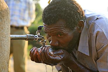 Burundi man drinking water from a standpipe, gitera.