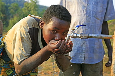 Burundi woman drinking water from a standpipe, gitera.