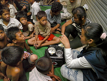 CAMBODI A Children receiving first aid by an outreach team of CSARO, central Phnom Penh
