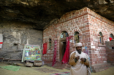 Religion, ethiopia. Na'akuto la'ab church, 7 kms from lalibela, built in a cave. The priest showing some of the church's treasures
