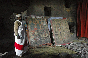 Religion, ethiopia. Na'akuto la'ab church, 7 kms from lalibela, built in a cave. The priest showing some of the church's treasures: an old painting, gondar style