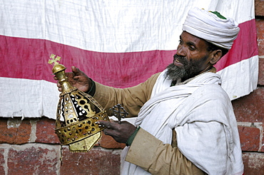 Religion, ethiopia. Na'akuto la'ab church, 7 kms from lalibela, built in a cave. The priest showing some of the church's treasures: with a crown