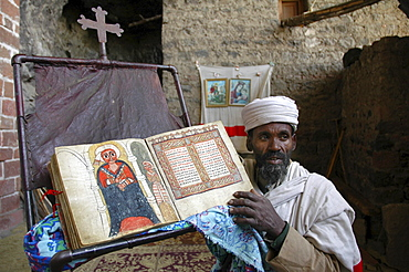 Religion, ethiopia. Na'akuto la'ab church, 7 kms from lalibela, built in a cave. The priest showing some of the church's treasures: with a manuscript book depicting the miracles of mary