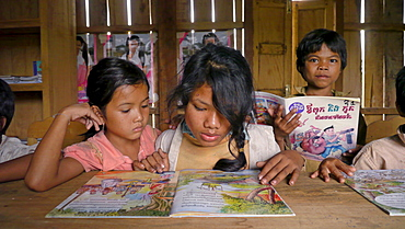 CAMBODIA Katot village, inhabited by the Prov tribal group, Stung Treng district. Library and literacy building provided by DPA and SCIAF. Children reading books