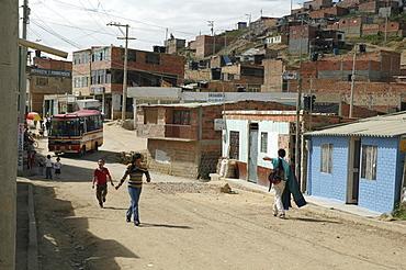 Colombia children running through the sprawling slum of altos de cazuca, bogota