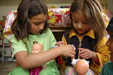 Colombia sisters playing with their dolls, the slum of altos de cazuca, bogota,