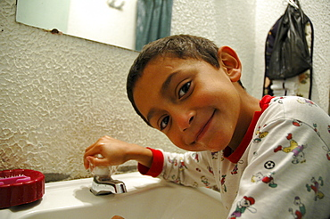 Colombia day in the life series: hugo andres, 7, of ciudad bolivar, bogota, brushing his teeth.