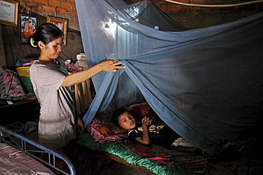 CAMBODIA 8-year-old Khoeun Sovan in bed under mosquito net, Mean Caeay slum, Phnom Penh