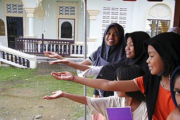 Thailand muslim girls catching raindrops. Pattani