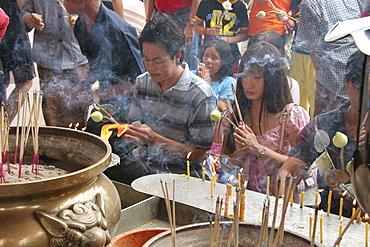 Thailand devotees praying and lighting incense. Ancient buddhist temple and stupa of phra pathom chedi, nakhon pathom