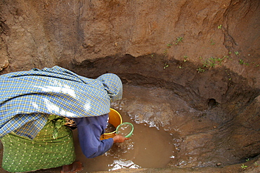 Tanzanian woman collecting unsafe and dirty drinking water from a water hole at kansay, near ngorongoro. She will carry the bucket of water 3 miles each way to and from her home. She and her family suffer from parasites and intestinal complaints because of the contaminated water