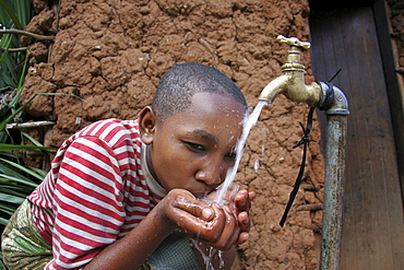 Tanzanian girl drinking water from the family tap. Mvango village, same, in the north-east near kilimanjaro
