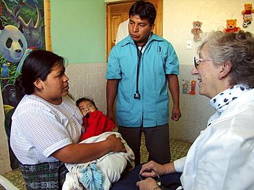 Guatemala nurse liz remily (right) attending to patients at her clinic in santa clara la laguna