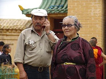 Mongolia old couple, man on cell phone, gandan buddhist monastery and temple, ulaan baatar
