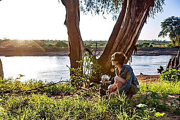 A young woman observes the early morning light while camping in Samburu National Park, Kenya, East Africa, Africa