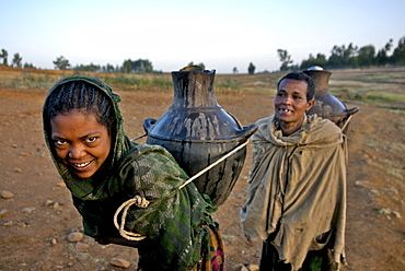 Women fetching water early in the morning. The wells in this area are empty during the dry season,forcing women to walk very long distance to fetch water in the nearest river bed. Ethiopia - 1195-16