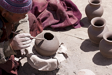 "Skalzang Norbu, 69, hand-builds ""bumpa"", or ritual vases, outside his home in Likir. Ladakh, India"