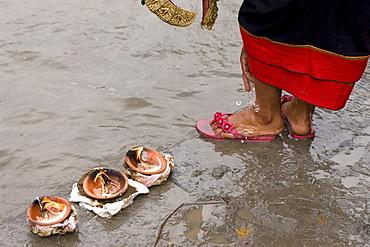 "Butter lamp offerings to the Bagmati River flowing next to Brahmayani Temple. Newar Village Women wears ""Haku Patasi"" to the Temple. (Haku Patasi is garb worn by Newari woman). Bhaktapur, Nepal"