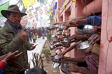 While circumambulating maha bodhi temple, tibetans making money offerings to bihari in need. Kalachakra initiation in bodhgaya, india