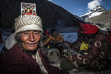 Pilgrim with a Buddha card on head at Dirapuk over Zutul Puk, Tibet, China, Asia