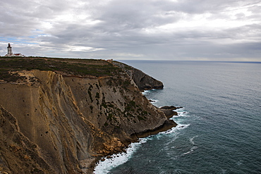 The Cabo Espichel coast on the Atlantic Ocean with lighthouse in the distance, Lisbon, Portugal, Europe