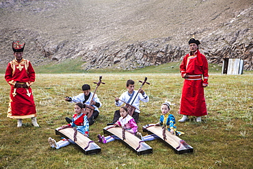 Boys playing Morin khuur (stringed instrument) (horse-head-violin) while young girls play Yatga-Yatuga (stringed instrument), Bunkhan, Mongolia, Central Asia, Asia