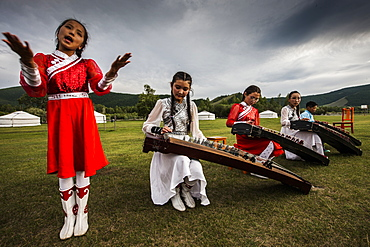 Concert at Lapis Sky Ger camp, young girls play Yatga-Yatuga (string instrument) at Bunkhan, Mongolia, Central Asia, Asia