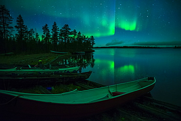 Beached canoes and Aurora Borealis and stars reflected in lake at night, Muonio, Lapland, Finland, Scandinavia, Europe
