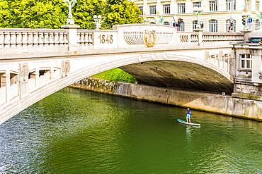 A boy paddle-boarding under Dragon Bridge, Ljubljana, Slovenia, Europe