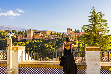 Woman taking a photo of Alhambra and Sierra Nevada mountains, Granada, Andalucia, Spain, Europe