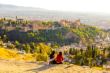 Two women looking at view of Alhambra and Sierra Nevada mountains, Granada, Andalucia, Spain, Europe