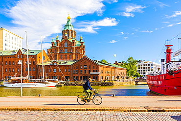 Uspenski Cathedral and cyclist by harbor in Helsinki, Uusimaa, Finland, Europe