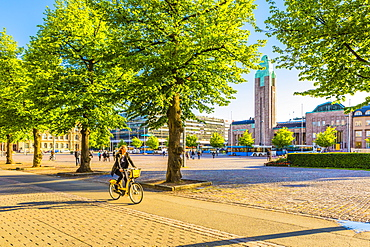 Young woman cycling by Helsinki Train Station in Helsinki, Uusimaa, Finland, Europe