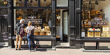 Tourists looking at display of food shop in Amsterdam, Netherlands, Europe