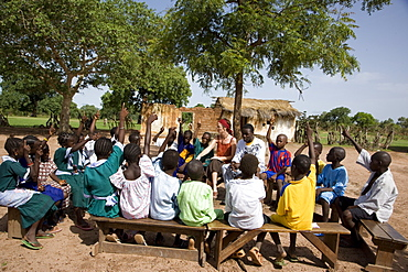 Volunteer Primary Cluster Teacher trainer, Fiona Stevenson leading story time and singing in the yard of primary school in Fori, next to trainee Alpha Ajallow,  The Gambia, West Africa, Africa