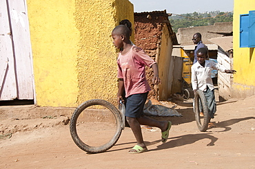 Boy running with bike tyre, Namuwongo slum area, Kampala, Uganda, Africa