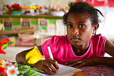 Young girl copying some work from the chalkboard at Kaindi demonstration school in Wewak, Papua New Guinea, Pacific