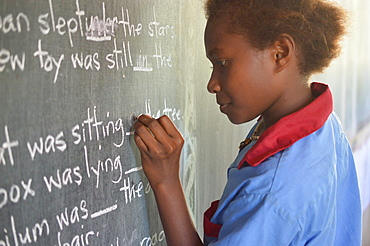 Young girl completing a gap filling exercise on a chalkboard at Malasang Primary School, Buka, Bougainville, Papua New Guinea, Pacific