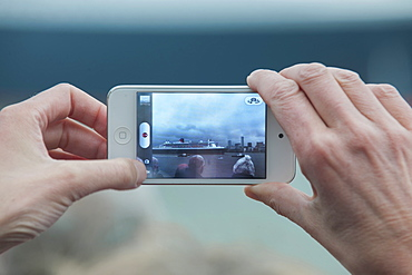 Hands photographing a Cunard cruise ship with an iPhone, United Kingdom, Europe