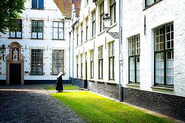 Nun at Begijnhof (Beguinage), Order of St. Benedict convent, Bruges, Belgium, Europe