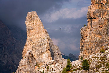 Adventure seeker high wire walking in Cinque Torri, Belluno, Dolomites, Italy, Europe