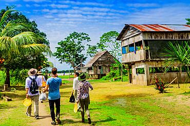 Tourists exploring a village in the Amazon Jungle, Pacaya Samiria National Reserve, Peru, South America