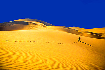 Woman walking away on sand dune, Huacachina Oasis, Peru, South America