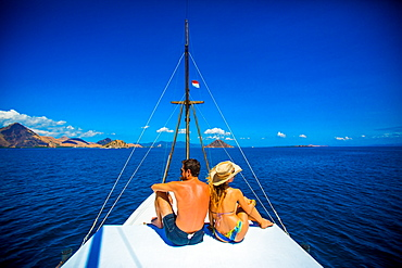 Couple relaxing on a Phinisi boat, Flores Island, Indonesia, Southeast Asia, Asia
