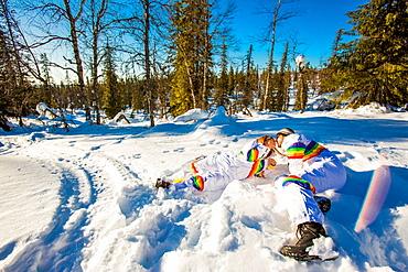 Couple kissing in matching Rainbow Ski Suits, Kakslauttanen Igloo West Village, Saariselka, Finland, Scandinavia, Europe