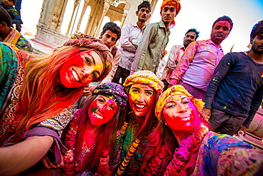 Female tourists stand in front of Temple during the pigment throwing Holi Festival, Vrindavan, Uttar Pradesh, India, Asia