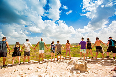 Group of people hold hands at the summit of Nohoch Mul Pyramid in the Ancient Mayan City of Coba, outside Tulum, Mexico, North America