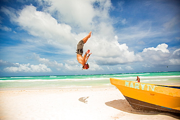 American Ninja Warrior Acrobat, Travis Brewer, does a back flip off a boat in Tulum, Mexico, North America