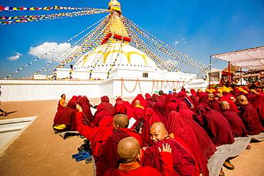 Buddhist monks praying around temple at Bouddha (Boudhanath), UNESCO World Heritage Site, Kathmandu, Nepal, Asia